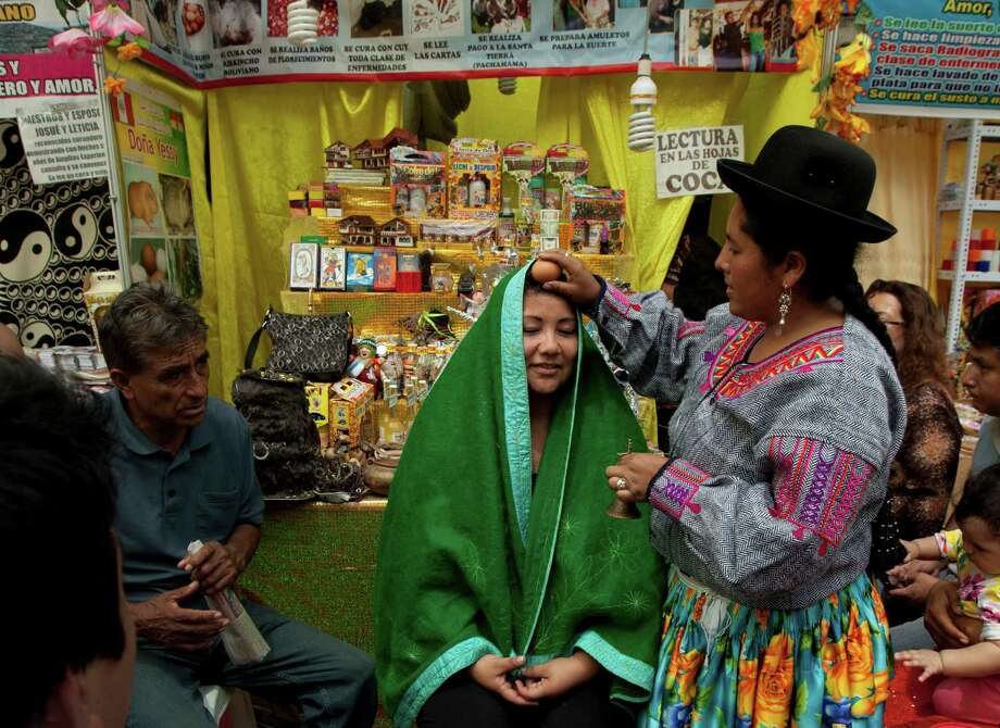 Shaman Yessy, right, performs a New Year's ritual to bring good luck to her client in the coming year, at the Market of Wishes in Lima, Peru. Photo: Martin Mejia