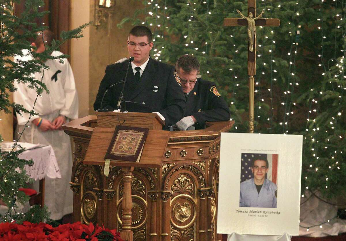West Webster firefighter Nick Volo, with support from West Webster Chaplain Hugh Knight, speaks of his friend and colleague Tomasz Kaczowka, during his funeral mass at St. Stanislaus Church in Rochester, New York, Monday Dec. 31, 2012. Kaczowka was killed along with firefighter Michael Chiapperini while responding to a fire in Webster, New York on Dec. 24, 2012, where William Spengler shot at first responders. Two other firefighters were injured while seven house burned.