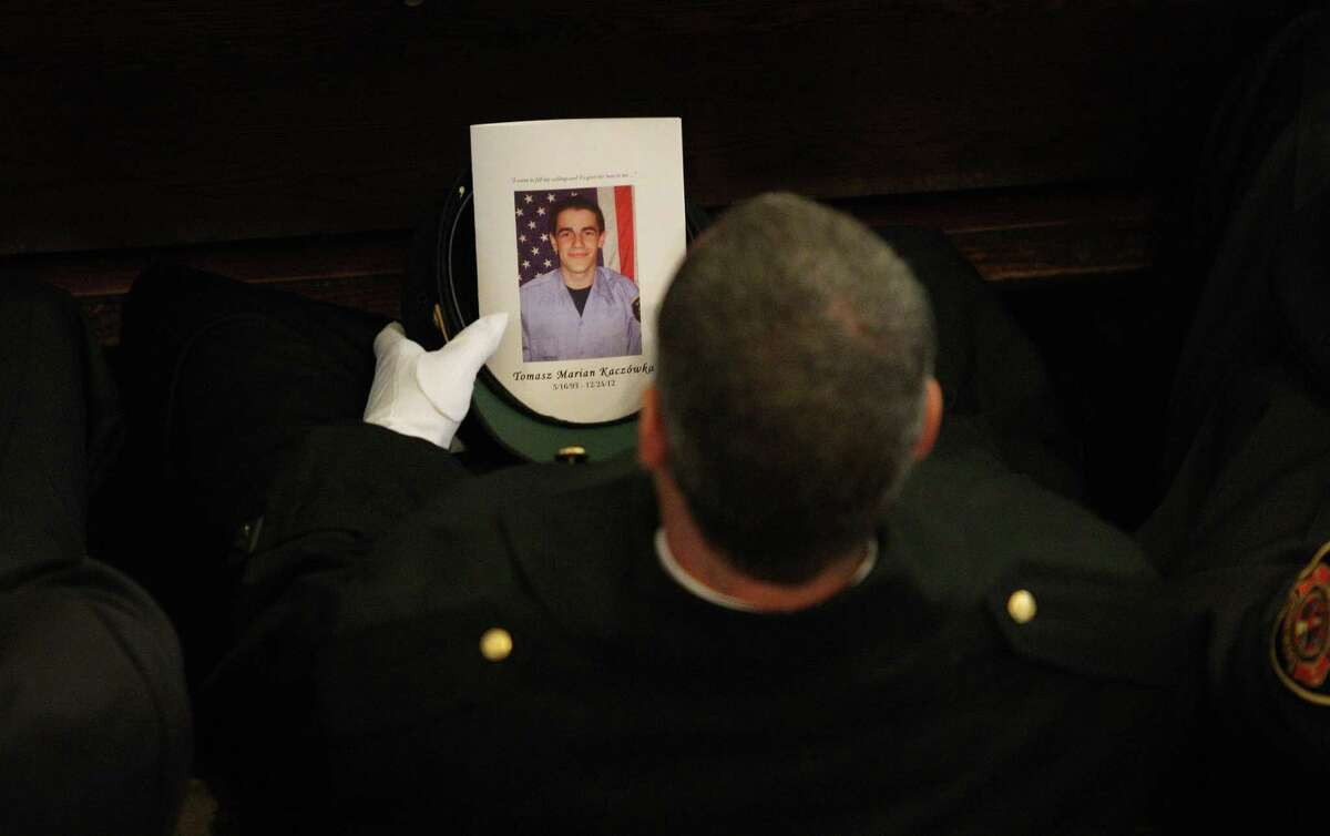 A West Webster firefighter carries a program during the funeral for fellow West Webster firefighter Tomasz Kaczowka at St. Stanislaus Church in Rochester, N.Y.,, Monday Dec. 31, 2012. Kaczowka was killed along with firefighter Michael Chiapperini while responding to a fire in Webster, New York on Dec. 24, 2012, where William Spengler shot at first responders. Two other firefighters were injured while seven house burned.