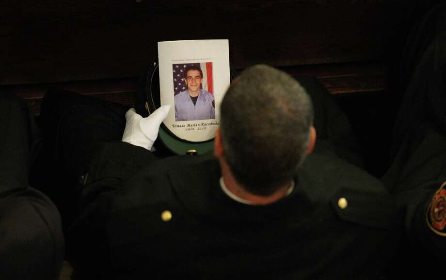A West Webster firefighter carries a program during the funeral for fellow West Webster firefighter Tomasz Kaczowka at St. Stanislaus Church in Rochester, N.Y.,, Monday Dec. 31, 2012.  Kaczowka was killed along with firefighter Michael Chiapperini  while responding to a fire  in Webster, New York on Dec. 24, 2012, where William Spengler shot at first responders. Two other firefighters were injured while seven house burned. Photo: Jamie Germano, AP / Democrat and Chronicle Pool