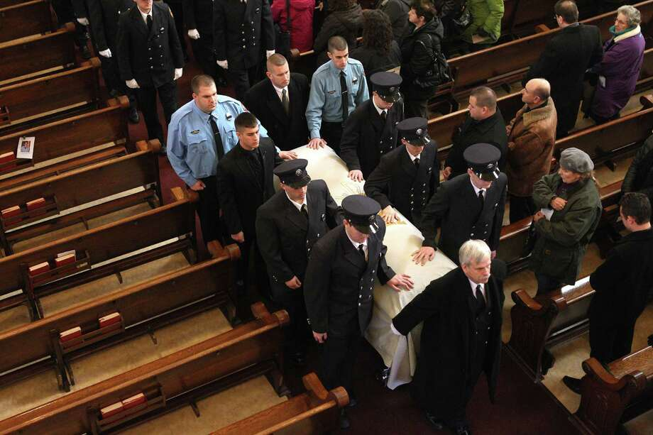 West Webster firefighters in procession with the  casket of fellow firefighter Tomasz Kaczowka during his funeral mass at St. Stanislaus Church in Rochester, New York, Monday Dec. 31, 2012.  Kaczowka was killed along with firefighter Michael Chiapperini  while responding to a fire in Webster, New York on Dec. 24, 2012, where William Spengler shot at first responders. Two other firefighters were injured while seven house burned. Photo: Jamie Germano, AP / Democrat and Chronicle Pool