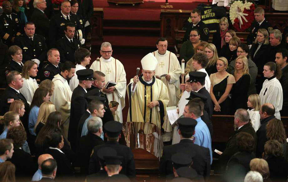 Bishop Emeritus Matthew H. Clark, center, prays during the funeral for West Webster firefighter Tomasz Kaczowka at St. Stanislaus Church in Rochester, New York, Monday Dec. 31, 2012.  Kaczowka was killed along with firefighter Michael Chiapperini  while responding to a fire  in Webster, New York on Dec. 24, 2012, where William Spengler shot at first responders. Two other firefighters were injured while seven house burned. Photo: Jamie Germano, AP / Democrat and Chronicle Pool