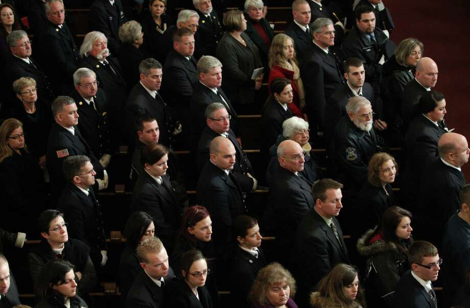 Mourners are seen during his funeral of Tomasz Kaczowka at St. Stanislaus Church in Rochester, New York,  Monday Dec. 31, 2012.  Kaczowka was killed along with firefighter Michael Chiapperini  while responding to a fire  in Webster, New York on Dec. 24, 2012, where William Spengler shot at first responders. Two other firefighters were injured while seven house burned. Photo: Jamie Germano, AP / Democrat and Chronicle Pool