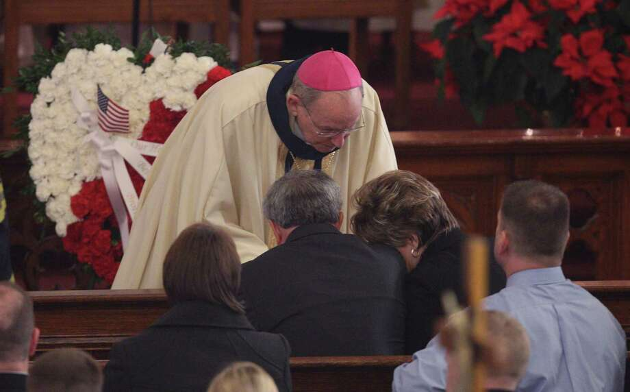 Bishop Emeritus Matthew H. Clark, shares his condolences with Marian and Janina Kaczowka during the funeral mass for their son, West Webster firefighter Tomasz Kaczowka at St. Stanislaus Church in Rochester, N.Y. Monday, Dec. 31, 2012. Kaczowka was killed along with firefighter Michael Chiapperini  while responding to a fire in Webster, New York on Dec. 24, 2012, where William Spengler shot at first responders. Two other firefighters were injured while seven house burned. Photo: Jamie Germano, AP / Democrat and Chronicle Pool