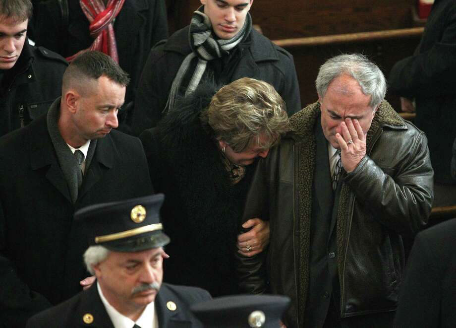 Janina and Marian Kaczowka, right, leave the church at the end of a funeral for their son, West Webster firefighter Tomasz Kaczowka, at St. Stanislaus Church in Rochester, New York, Monday Dec. 31, 2012. Kaczowka was killed along with firefighter Michael Chiapperini  while responding to a fire in Webster, New York on Dec. 24, 2012, where William Spengler shot at first responders. Two other firefighters were injured while seven house burned. Photo: Jamie Germano, AP / Democrat and Chronicle Pool