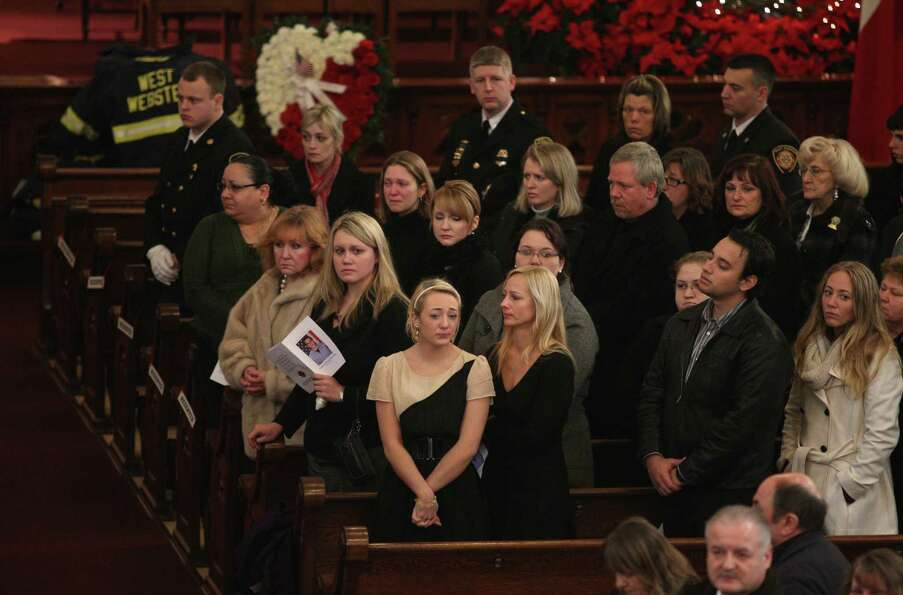 Mourners grieve during the funeral of Tomasz Kaczowka at St. Stanislaus Church in Rochester, N.Y.,,