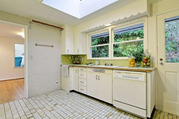 Kitchen of 11255 Exeter Ave. N.E. The 2,180-square-foot house, built in 1949, has three bedrooms, 1.75 bathrooms, two fireplaces, a downstairs family room with a bar, and a deck on a 9,383-square-foot lot one block from the Burke-Gilman Trail. It's listed for $399,000. Photo: Courtesy Jan Snook/Windermere Real Estate