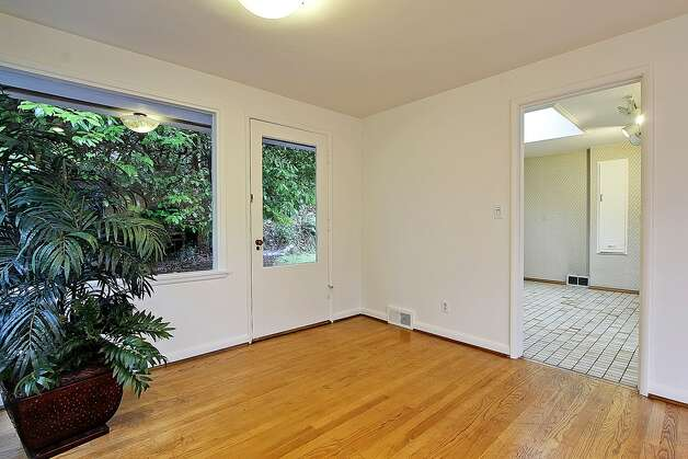 Dining room of 11255 Exeter Ave. N.E. The 2,180-square-foot house, built in 1949, has three bedrooms, 1.75 bathrooms, two fireplaces, a downstairs family room with a bar, and a deck on a 9,383-square-foot lot one block from the Burke-Gilman Trail. It's listed for $399,000. Photo: Courtesy Jan Snook/Windermere Real Estate