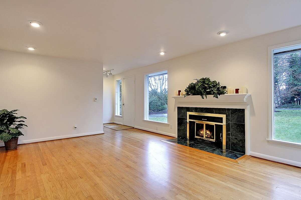 Living room of 11255 Exeter Ave. N.E. The 2,180-square-foot house, built in 1949, has three bedrooms, 1.75 bathrooms, two fireplaces, a downstairs family room with a bar, and a deck on a 9,383-square-foot lot one block from the Burke-Gilman Trail. It's listed for $399,000.