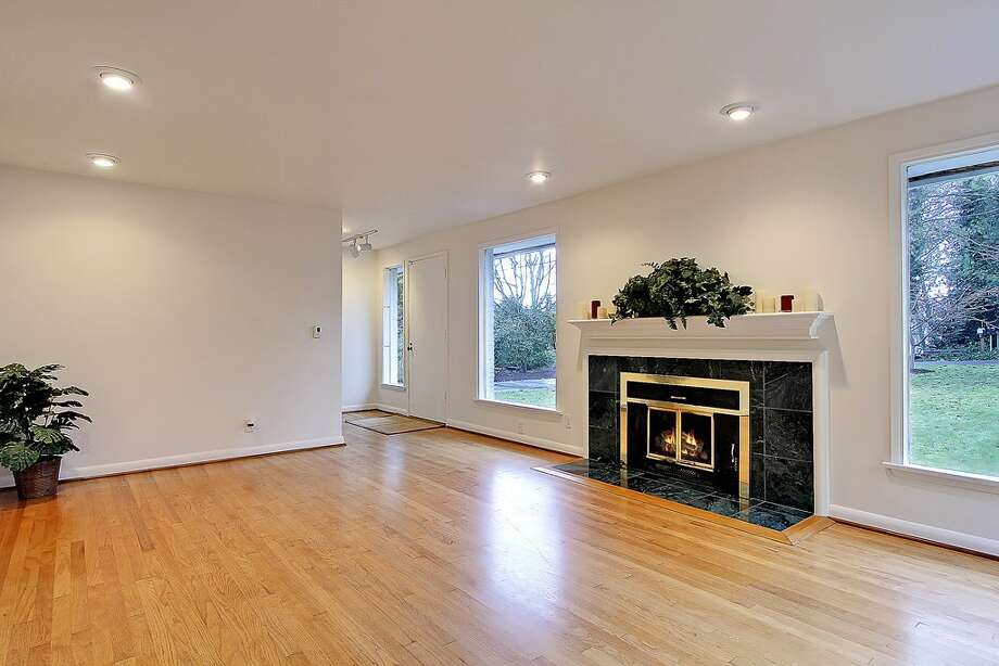 Living room of 11255 Exeter Ave. N.E. The 2,180-square-foot house, built in 1949, has three bedrooms, 1.75 bathrooms, two fireplaces, a downstairs family room with a bar, and a deck on a 9,383-square-foot lot one block from the Burke-Gilman Trail. It's listed for $399,000. Photo: Courtesy Jan Snook/Windermere Real Estate