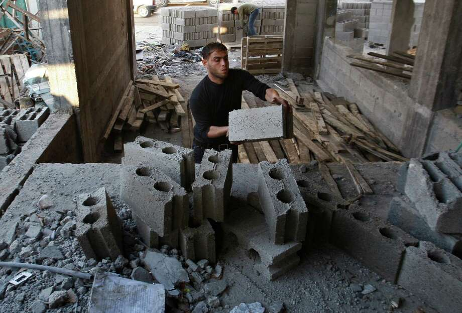 """Palestinian workers rebuild a house in Gaza City, Monday, Dec. 31, 2012. Israel has started allowing long-banned building materials into the Gaza Strip, its first key concession to the territory's Hamas rulers under a cease-fire that ended eight days of intense fighting last month, the military said Monday. A Hamas official described the quantity sent so far as """"cosmetic"""" and Gaza economists said it would take years of round-the-clock shipments to even make a dent in the gap left by the five years of blockade. (AP Photo/Hatem Moussa) Photo: Hatem Moussa"""