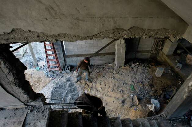 "A Palestinian worker rebuilds a house in Gaza City, Monday, Dec. 31, 2012. Israel has started allowing long-banned building materials into the Gaza Strip, its first key concession to the territory's Hamas rulers under a cease-fire that ended eight days of intense fighting last month, the military said Monday. A Hamas official described the quantity sent so far as ""cosmetic"" and Gaza economists said it would take years of round-the-clock shipments to even make a dent in the gap left by the five years of blockade. (AP Photo/Hatem Moussa) Photo: Hatem Moussa"