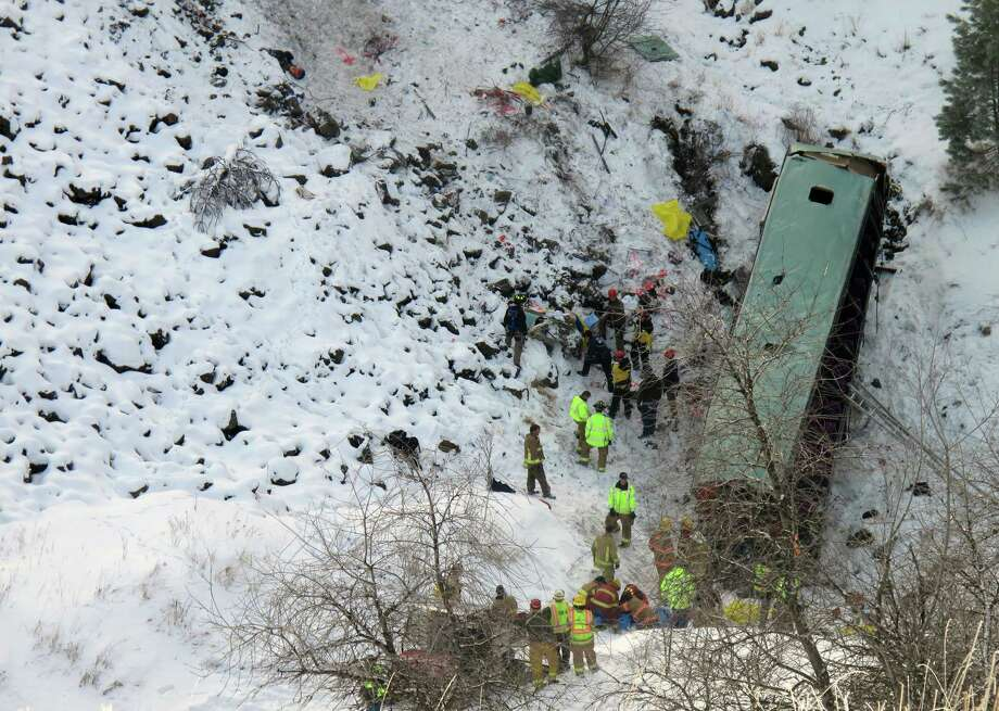 Emergency personnel respond to the scene of a multiple fatality accident where a tour bus careened through a guardrail along an icy Oregon highway and several hundred feet down a steep embankment, authorities said, Sunday, Dec. 30, 2012 about 15 miles east of Pendleton, Ore. The charter bus carrying about 40 people lost control around 10:30 a.m. on the snow- and ice-covered lanes of Interstate 84, according to the Oregon State Police. (AP Photo/East Oregonian, Tim Trainor) Photo: Tim Trainor