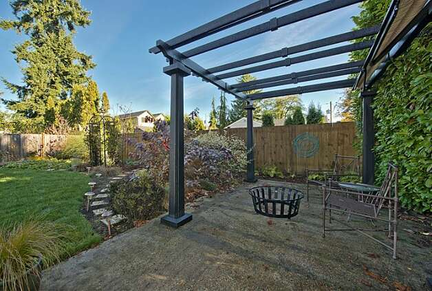 Backyard patio of 12514 25th Ave. N.E. The 1,830-square-foot house, built in 1924, has three bedrooms, 1.75 bathrooms, an updated kitchen and a shed on an 8,438-square-foot lot. It's listed for $439,950. Photo: Courtesy April Rauch And Mark Emily/Windermere Real Estate