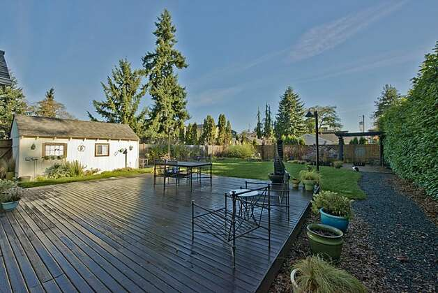 Backyard deck of 12514 25th Ave. N.E. The 1,830-square-foot house, built in 1924, has three bedrooms, 1.75 bathrooms, an updated kitchen and a shed on an 8,438-square-foot lot. It's listed for $439,950. Photo: Courtesy April Rauch And Mark Emily/Windermere Real Estate