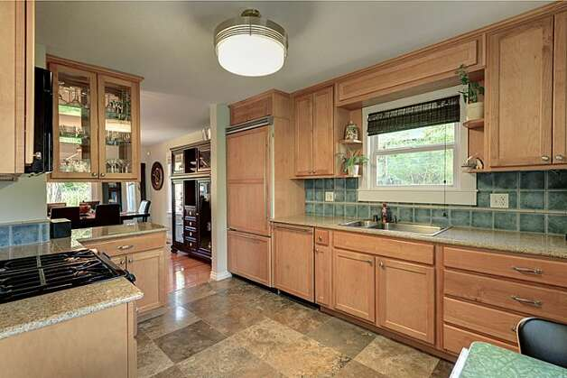 Kitchen of 12514 25th Ave. N.E. The 1,830-square-foot house, built in 1924, has three bedrooms, 1.75 bathrooms, a backyard deck and patio, and a shed on an 8,438-square-foot lot. It's listed for $439,950. Photo: Courtesy April Rauch And Mark Emily/Windermere Real Estate