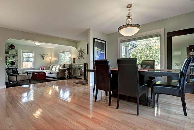 Dining and living rooms of 12514 25th Ave. N.E. The 1,830-square-foot house, built in 1924, has three bedrooms, 1.75 bathrooms, an updated kitchen, a backyard deck and patio, and a shed on an 8,438-square-foot lot. It's listed for $439,950. Photo: Courtesy April Rauch And Mark Emily/Windermere Real Estate