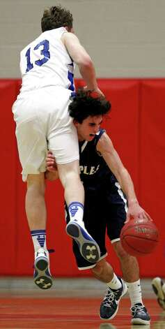 Darien's Liam Naughton (13) collides with Staples' James Frusciante  during the first half of the championship game of the Tony LaVista Basketball Tournament Monday, Dec. 31, 2012, in New Canaan, Conn. ( Brett Coomer / Hearst Newspapers ) Photo: Brett Coomer, Brett Coomer/Hearst Newspapers / The News-Times