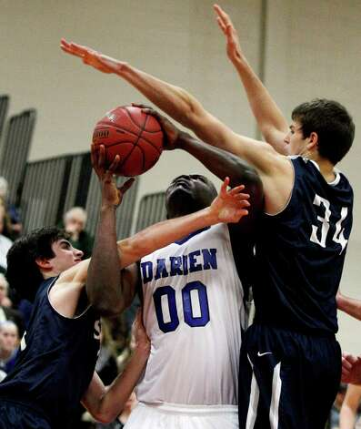 Darien's Chima Azouonwu (00) looks for a shot as he is defended by Staples James Frusciante, left, and Alex Addessi (34) during the second half of the championship game of the Tony LaVista Basketball Tournament Monday, Dec. 31, 2012, in New Canaan, Conn. Darien beat Staples 50-47. ( Brett Coomer / Hearst Newspapers ) Photo: Brett Coomer, Brett Coomer/Hearst Newspapers / The News-Times