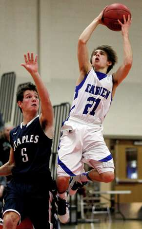 Darien's Matt Staubi (21) takes a shot with Staples' Joe Greenwald (5) defending during the second half of the championship game of the Tony LaVista Basketball Tournament Monday, Dec. 31, 2012, in New Canaan, Conn. Darien beat Staples 50-47. ( Brett Coomer / Hearst Newspapers ) Photo: Brett Coomer, Brett Coomer/Hearst Newspapers / The News-Times