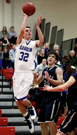 Darien's Ian Burgoyne (32) takes a shot past Staples' Ross Whelan (24) during the second half of the championship game of the Tony LaVista Basketball Tournament Monday, Dec. 31, 2012, in New Canaan, Conn. Darien beat Staples 50-47. ( Brett Coomer / Hearst Newspapers ) Photo: Brett Coomer, Brett Coomer/Hearst Newspapers / The News-Times