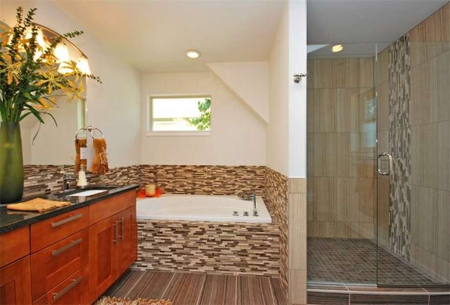 Master bathroom of 12036 25th Ave. N.E. The 2,100-square-foot house, built in 2012, has four bedrooms, three bathrooms, a floating staircase, a deck and a two-car garage on a 7,274-square-foot lot. It's listed for $499,000. Photo: Deborah Arends/RE/MAX Northwest Realtors