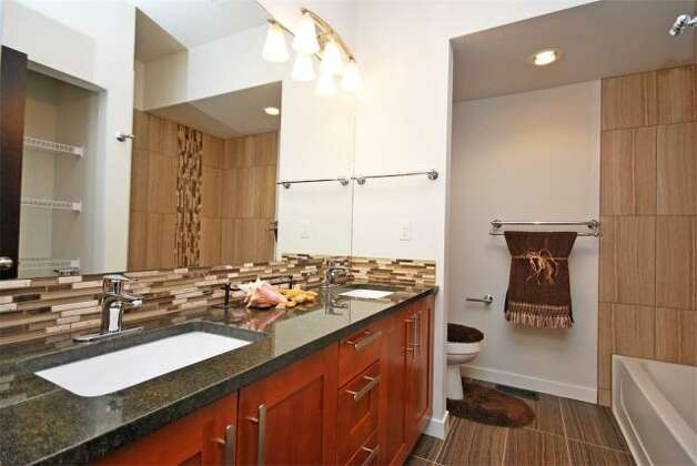 Bathroom of 12036 25th Ave. N.E. The 2,100-square-foot house, built in 2012, has four bedrooms and three bathrooms -- including a master suite with a five-piece bathroom -- a floating staircase, a deck and a two-car garage on a 7,274-square-foot lot. It's listed for $499,000. Photo: Deborah Arends/RE/MAX Northwest Realtors