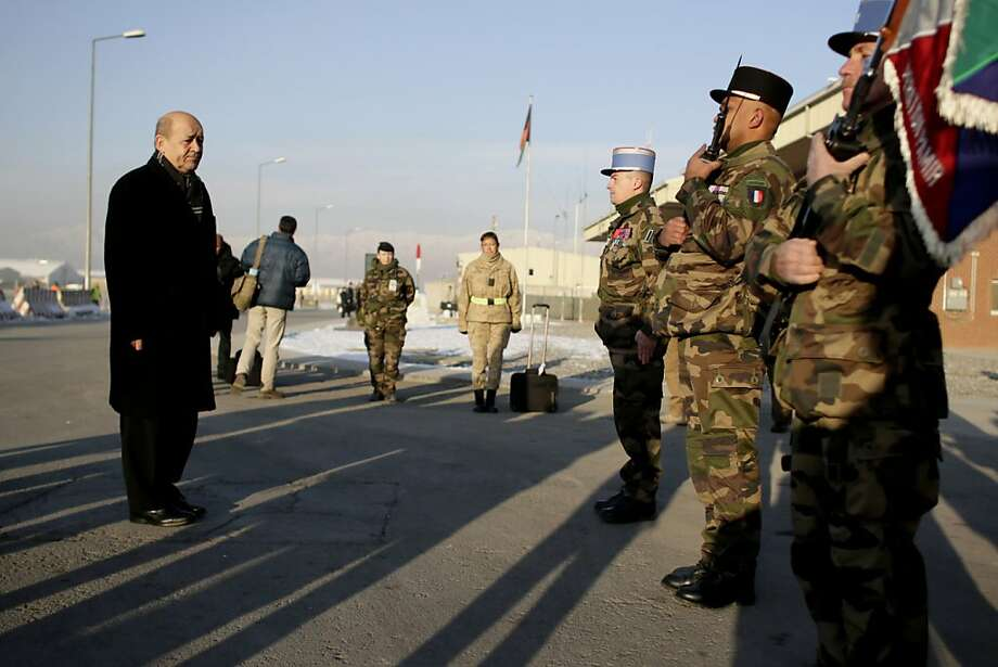 French Defense Minister Jean-Yves Le Drian (left) looks at troops after arriving at the Kabul airport. He is scheduled to meet Afghan President Hamid Karzai during his visit. Photo: Kenzo Tribouillard, AFP/Getty Images