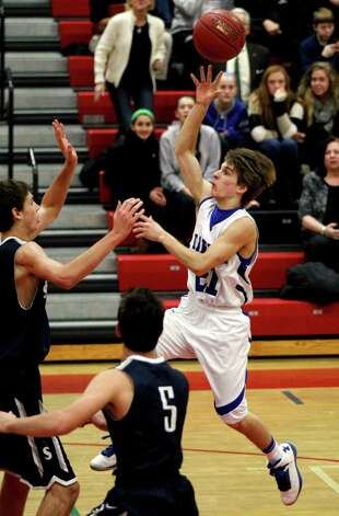 Darien's Matt Staubi (21) leaps past Staples' Joe Greenwald (5) for a score during the second half of the championship game of the Tony LaVista Basketball Tournament Monday, Dec. 31, 2012, in New Canaan, Conn. Darien beat Staples 50-47. ( Brett Coomer / Hearst Newspapers ) Photo: Brett Coomer, Brett Coomer/Hearst Newspapers / The News-Times