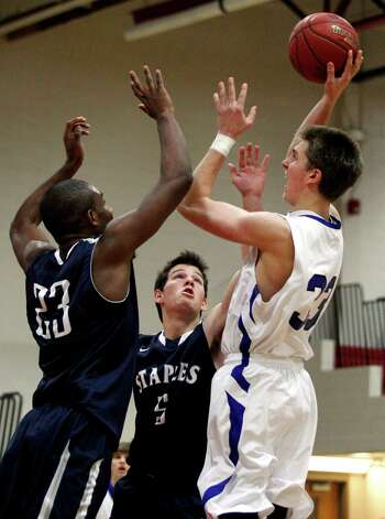 Darien's Ames Murray (33) takes a shot over Staples' Darryle Wiggins (23) and Joe Greenwald (5) during the second half of the championship game of the Tony LaVista Basketball Tournament Monday, Dec. 31, 2012, in New Canaan, Conn. Darien beat Staples 50-47. ( Brett Coomer / Hearst Newspapers ) Photo: Brett Coomer, Brett Coomer/Hearst Newspapers / The News-Times