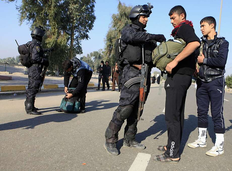 Iraqi police search Shiites on an annual religious pilgrimage to the city of Karbala. Insurgent attacks on Shiites are common despite tight security. Photo: Karim Kadim, Associated Press