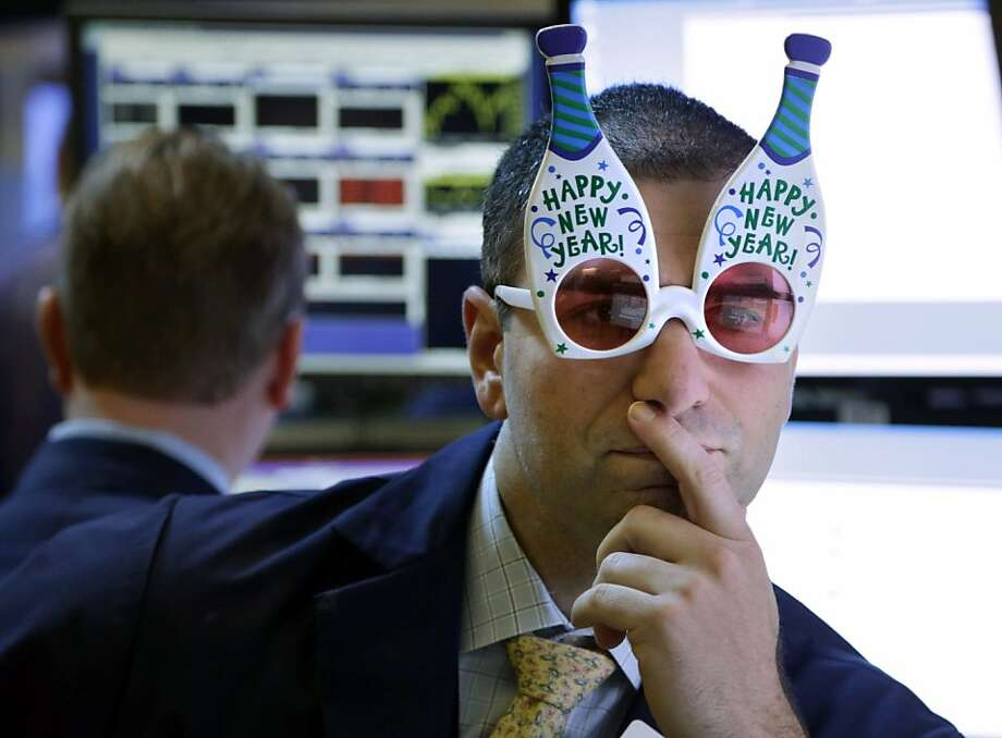 "A trader wearing holiday glasses works on the New York Stock Exchange floor on Monday. The market struggled for direction, then rose at a fleeting moment of hope for a deal to avert the ""fiscal cliff."" Photo: Seth Wenig, Associated Press"