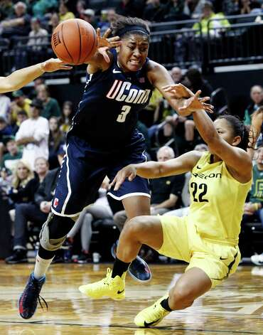Connecticut forward Morgan Tuck, left, is fouled on her way to the basket by Oregon guard Ariel Thomas during the second half of an NCAA college basketball game in Eugene, Ore., Monday, Dec. 31, 2012. Connecticut won 95-51. (AP Photo/Don Ryan) Photo: Don Ryan, Associated Press / AP