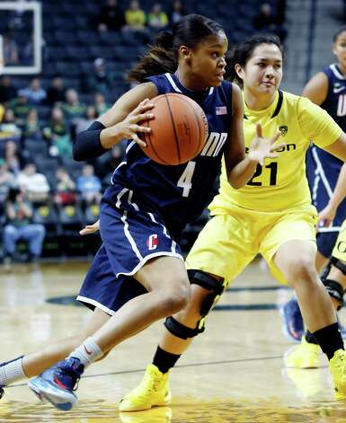 Connecticut guard Moriah Jefferson, left, drives to the basket past Oregon guard Amanda Delgado during the second half of an NCAA college basketball game in Eugene, Ore., Monday, Dec. 31, 2012. Connecticut won 95-51. (AP Photo/Don Ryan) Photo: Don Ryan, Associated Press / AP