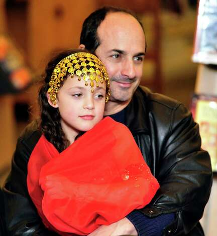 "Raymond Ganim and his daughter, Jillian, 7, watch Careesah perform during ""Belly Dancing for Kids,"" a First Night performance at the Danbury Library Monday, Dec. 31, 2012. Photo: Michael Duffy"