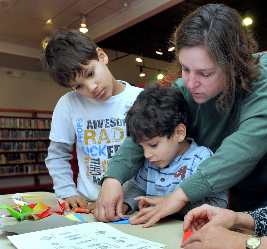 At the Ridgefield Library, Colleen Broderick, of Ridgefield, helps her sons, Kian, 9, left, and Caden, 4, make origami cranes that will be sent to students in Newtown, Monday, Dec. 31, 2012. Photo: Carol Kaliff / The News-Times
