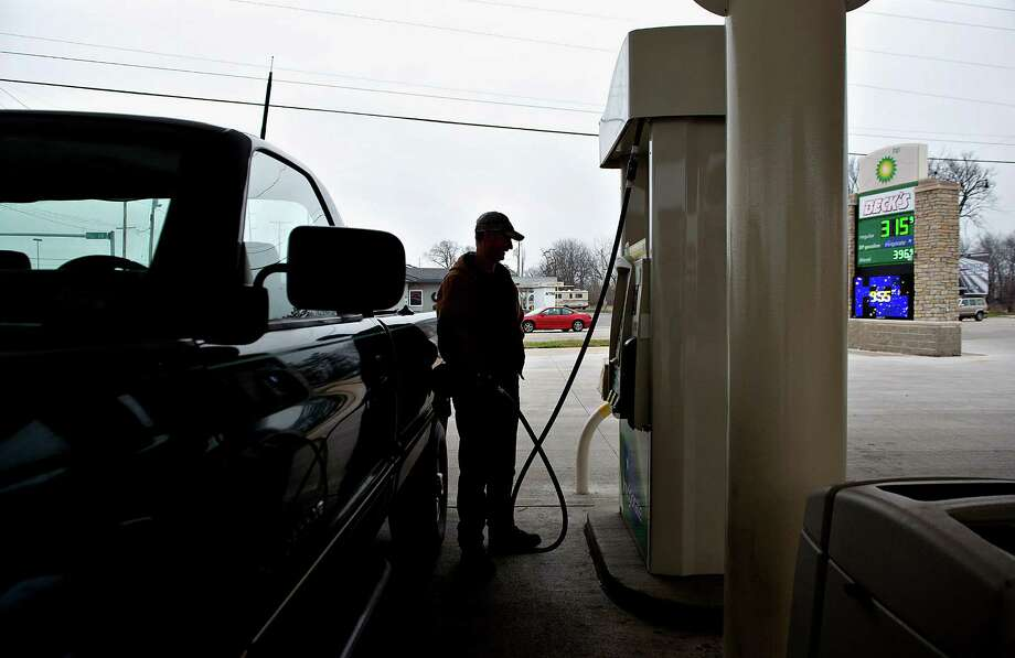 Gas prices are displayed, right, as customer Lester Behrends fills his truck with fuel at a gas station in Princeton, Illinois, U.S., on Tuesday, Dec. 18, 2012. Retail gasoline in the U.S. fell to the lowest level in a year as refineries restored production and stockpiles rose to an eight-month high, blunting criticism of President Barack Obama's energy policies. Photographer:  Daniel Acker/Bloomberg *** Local Caption *** Lester Behrends Photo: Daniel Acker, Bloomberg / © 2012 Bloomberg Finance LP