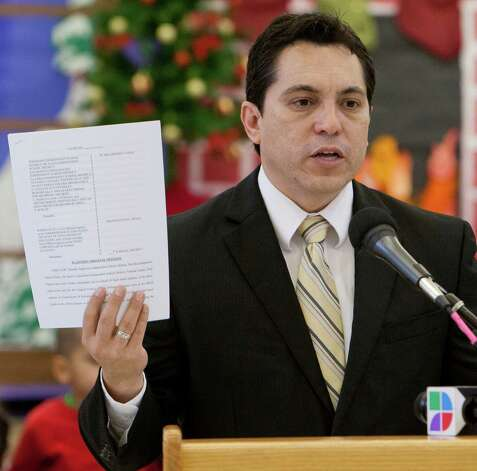 David G. Hinojosa, MALDEF southwest regional counsel, holds a copy of the lawsuit that will be filed on behalf of low wealth school districts, during a press conference, Tuesday, Dec. 13, 2011, in San Antonio. Photo: Darren Abate, SPECIAL TO THE EXPRESS-NEWS / SAN ANTONIO EXPRESS-NEWS
