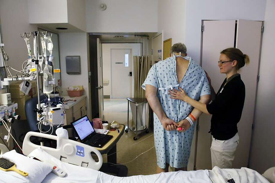 Kendra Johnson, who hopes to land a primary care residency, checks on Greg Little in his room at UCSF Medical Center. Photo: Carlos Avila Gonzalez, The Chronicle