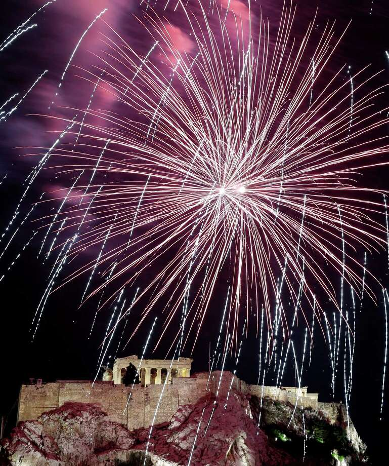 Fireworks explode over the ancient Acropolis Hill with the Parthenon temple during the New Year's celebrations in Athens, on Tuesday Jan. 1, 2013. (AP Photo/Dimitri Messinis) Photo: Dimitri Messinis, Associated Press / AP