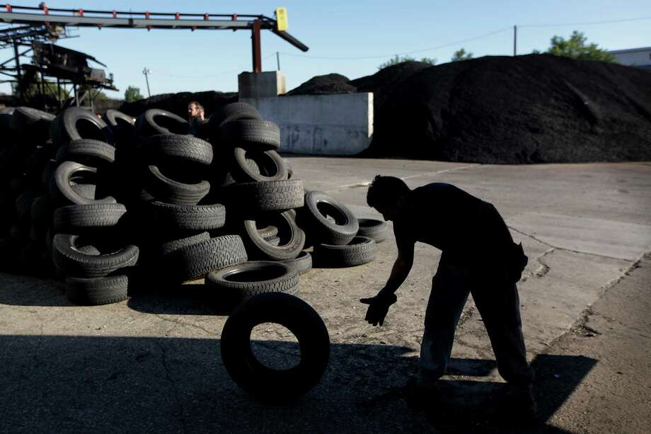 Employee loads good tires to be sold in secondary market, after inspection at Liberty Tire Recycling, and spared recycling shredding process on Friday, Nov. 16, 2012, in Baytown. Liberty Tire Recycling is the largest tire processor in the country that shreds half of all the tires people discard every year, but they are now going to face competition from a new Houston plant that promises a cleaner, more modern recycling process. Photo: Mayra Beltran, Houston Chronicle / © 2012 Houston Chronicle