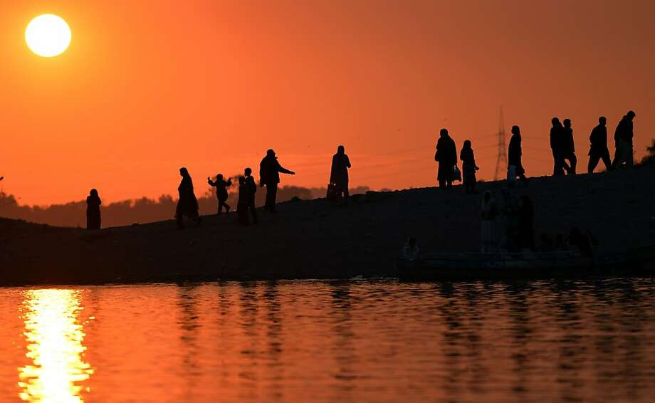 Watching the 'ball' go down: Pakistanis take in the last sunset of 2012 at a lake in Islamabad. Photo: Aamir Qureshi, AFP/Getty Images
