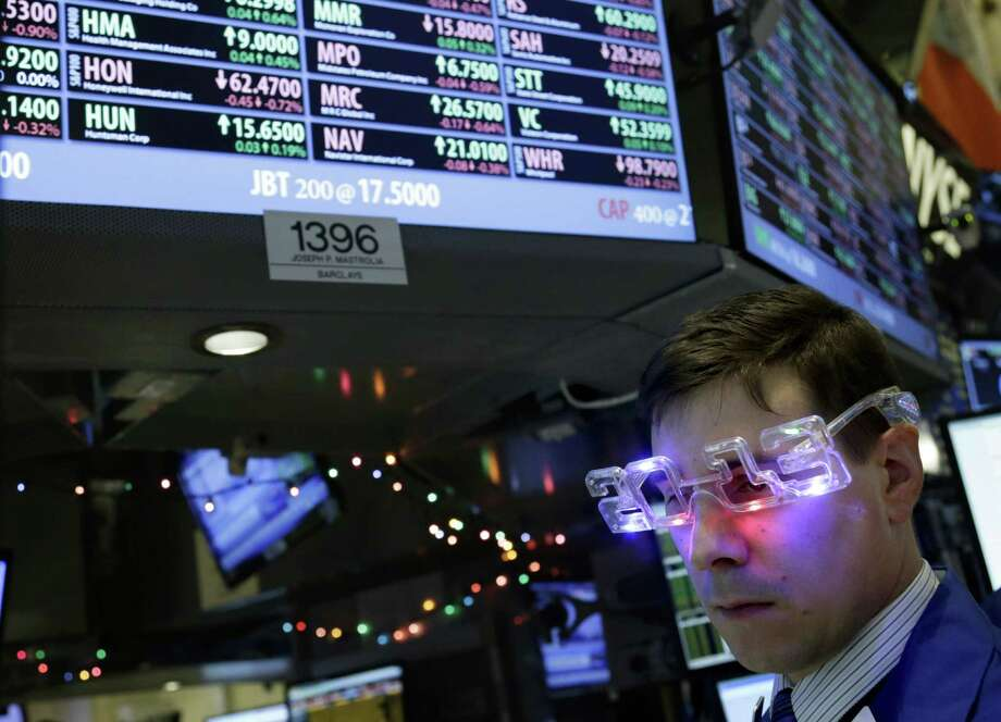 """A trader wearing """"2013"""" glasses works Monday on the floor at the New York Stock Exchange. The Standard & Poor's 500 index rose 13.4 percent for the year. Photo: Seth Wenig, STF / AP"""