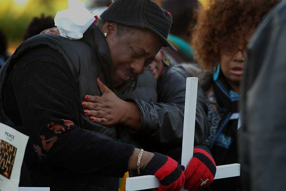 Mallie Latham (left) is comforted by Traci Stamps as he grieves for his slain daughter, Shanika Latham, during a memorial service at St. Columba Catholic Church in Oakland for all of the 131 people killed in the city this year. Photo: Lacy Atkins, The Chronicle