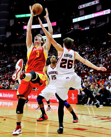 Rockets center Omer Asik gets a rebound over Kyle Korver of the Hawks. Photo: BOB LEVEY