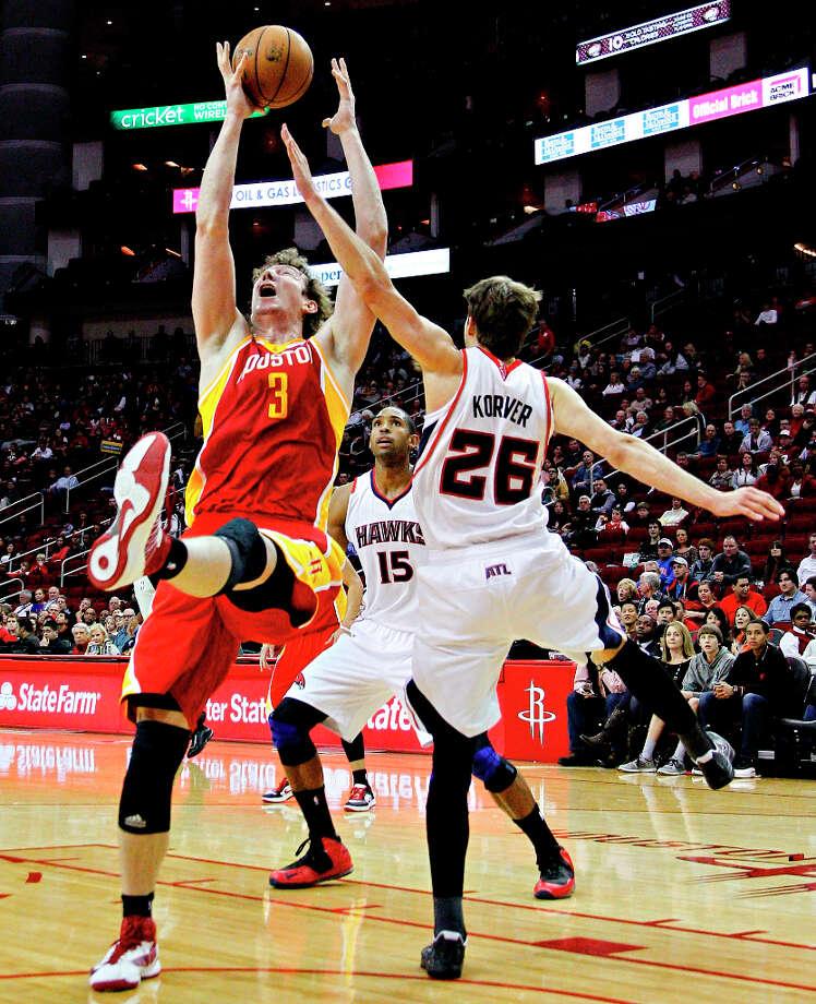 Rockets center Omer Asik gets a rebound over Kyle Korver of the Hawks. Photo: BOB LEVEY