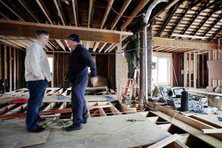 In a Thursday, Dec. 20, 2012 photo, Joseph O'Grady, left, with Rockaway Reach, talks with Kevin Murphy as they discuss the renovation of Murphy's home in the Belle Harbor neighborhood of New York.  Murphy's house was heavily damaged by flooding sea water during Superstorm Sandy on Oct. 29, 2012. More than 160 organizations and counting have gotten shares of the Sandy relief funds collected so far by the Robin Hood Foundation. Rockaway Reach works on behalf of Catholic Charities of San Diego, which has received funding from the Robin Hood Foundation. (AP Photo/Mark Lennihan) Photo: Mark Lennihan