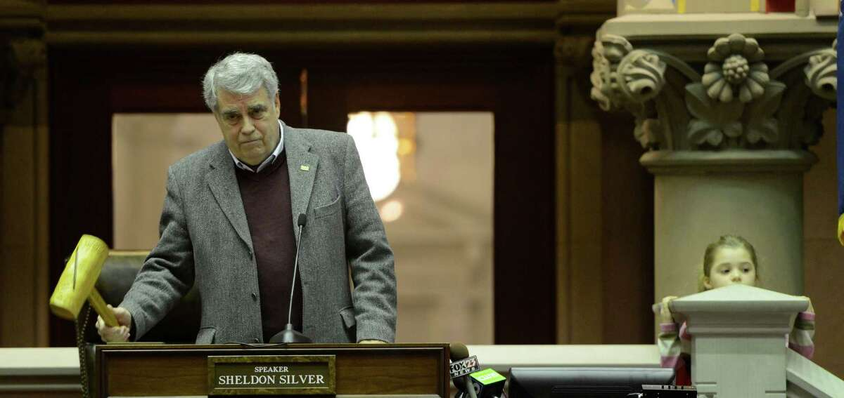 Jack McEneny, left does his final official duty as an Assemblyman by gaveling out the daily session as his granddaughter Madeline Spencer peers above a pillar in the Assembly Chamber of the State Capitol in Albany, N.Y. Dec 31, 2012. (Skip Dickstein/Times Union)