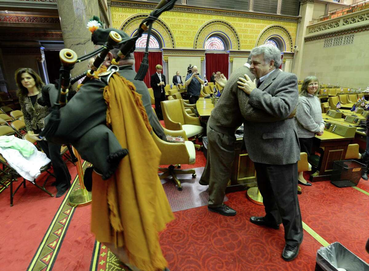 Jack McEneny, right, is piped from out of the chamber by Peter Lounsbery, right after performing his final official duty as an Assemblyman by gaveling out the daily session in the Assembly Chamber of the State Capitol in Albany, N.Y. Dec 31, 2012. (Skip Dickstein/Times Union)