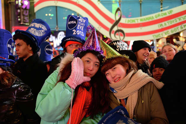 Revelers gather on Times Square on December 31, 2012 in New York City, where as many as a million people are expected to celebrate New Year's by viewing the traditional drop of a giant crystal ball -- and a billion more watching on TV around the world.    With just a few hours to go before 2013, huge crowds assembled under the Manhattan neighborhood's famous neon advertising hoardings.    AFP PHOTO / Emmandel DUNAND Photo: EMMANUEL DUNAND, AFP/Getty Images / 2013 AFP